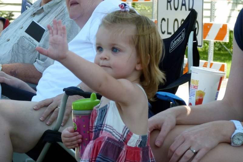 Charlotte waving at the people in the parade